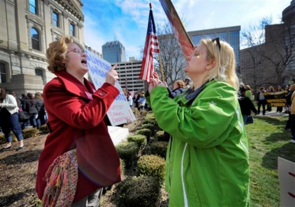 In this 2011 file photo, Planned Parenthood supporter Peg Paulson of Carmel, Ind., left, and opponent Heather Pruett of Indianapolis argue during a rally at the Indiana Statehouse on the South Lawn in Indianapolis in response to an Indiana House bill which would end funding to Planned Parenthood because it provides abortions.