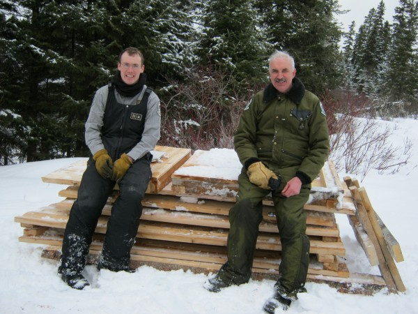 AWW Ranger Patrick Emery (left) and AWW Superintendent Matt LaRoche sit on a stack of pre-fabricated wood parts for winter hauling into the Allagash Wilderness Waterway.