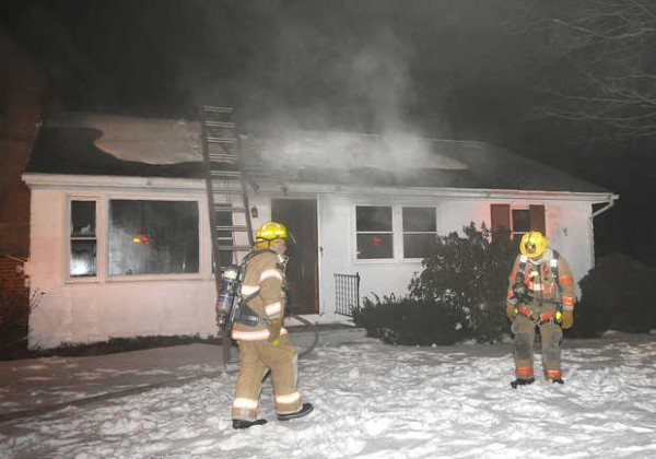 Lewiston firefighters work at the scene of a house fire at 72 Wellman St. in Lewiston on Saturday.