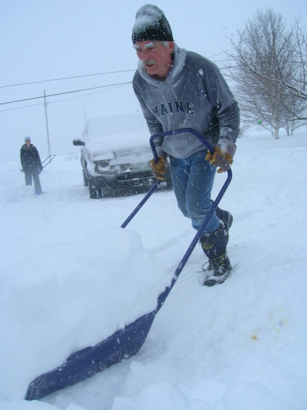 Kurt Wickenheiser of Madawaska uses a scrape to clear snow from his driveway during Saturday's snowstorm. At least a foot of snow had fallen in far northern Maine, with the white stuff still coming down at 9:30 a.m. Feb. 25, 2012.
