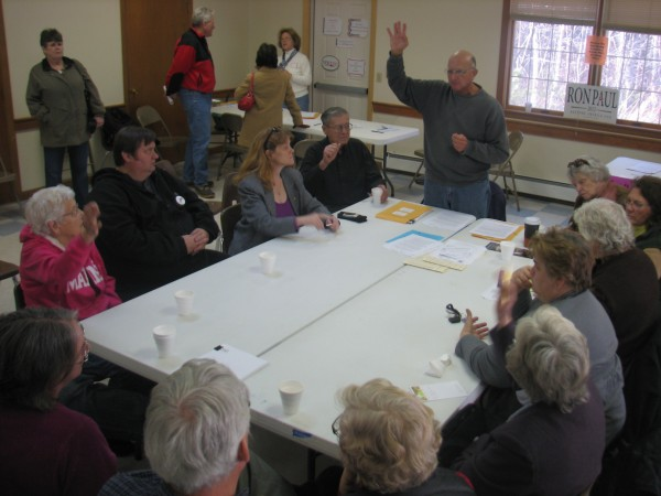 Tremont Republican Party Chairman Ben Harper, with hand raised, calls for a vote during the Mount Desert Island GOP caucus Saturday, Feb. 4, 2012, at the fire station in the Mount Desert village of Somesville. About 60 MDI residents attended the gathering, but the state Republican organization has said it intends not to announce which GOP candidate gets the most support at the party's caucuses until Feb. 11.