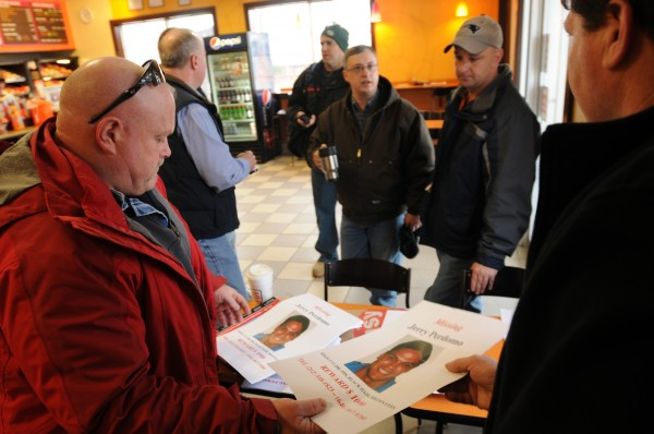 Seminole County firefighter Troy Todak passes out posters to Bangor firefighter John Higgins at Dunkin Donuts on Odlin Road in Bangor on Monday. Bangor firefighters fanned out into Waldo and Kennebec counties to hang the posters in an attempt to locate missing Florida firefighter Jerry Perdomo, who was last seen Feb. 16, 2012.