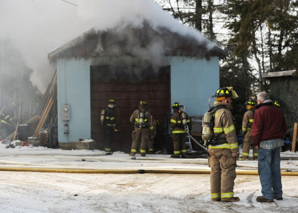 Dan Lane (right) talks with a firefighter as other firefighters work to open a garage owned by Lane on the Monroe Road in Hampden on Monday, Feb 13, 2012. Crews from nunerous towns responded. Some difficulty occurred when a stalling saw slowed a hole being cut in the garage door. Lane, who owns a building company said he used the garage to store tools.