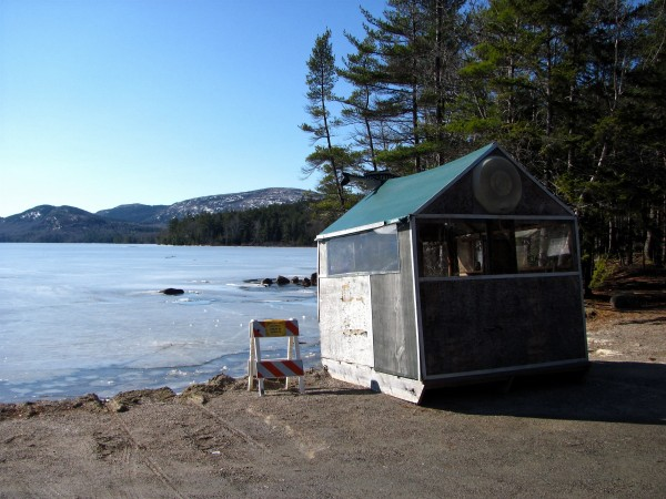 An ice fishing shack sits on dry land next to Eagle Lake in Acadia National Park on Sunday, Feb. 26, 2012, while a sign warns visitors about potentially unsafe ice conditions. Numerous ice fishing derbies, including the state's largest on Sebago Lake, have been canceled this winter, which is affecting the charities and community organizations that benefit from the wintertime fundraisers.