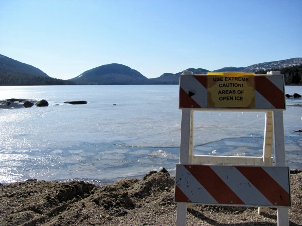 A sign warns visitors about potentially unsafe ice conditions on Eagle Lake in Acadia National Park on Sunday, Feb. 26, 2012. Numerous ice fishing derbies, including the state's largest on Sebago Lake, have been canceled this winter, which is affecting the charities and community organizations that benefit from the wintertime fundraisers.