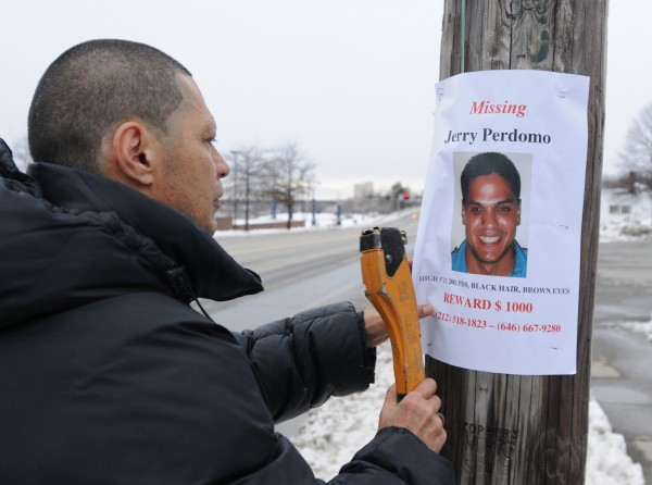 Jerry Perdomo Sr. tacks a missing person poster on a telephone pole outside the Bangor Fire Department's central station on Saturday, Feb. 25, 2012. Perdomo's son, Jerry Perdomo Jr. has been missing since Feb. 16, 2012.
