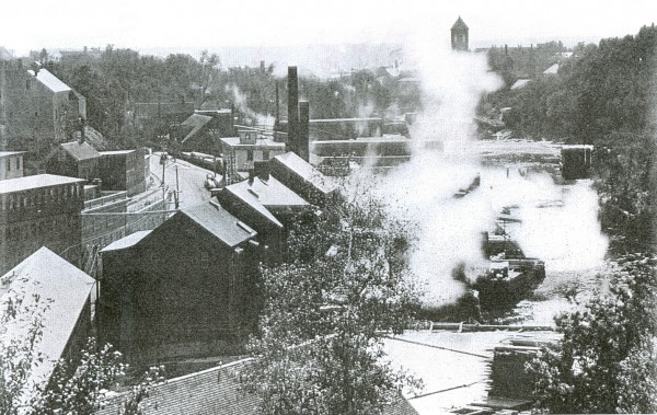 Morse and Company stretched along the Kenduskeag Stream, one of the area's last large sawmill operations. It produced lumber as well as a variety of wood products ranging from staircases to fireplace mantels for use in home construction. The tower of the old Bangor city hall (top right) at Hammond and Columbia streets can be seen in the distance.