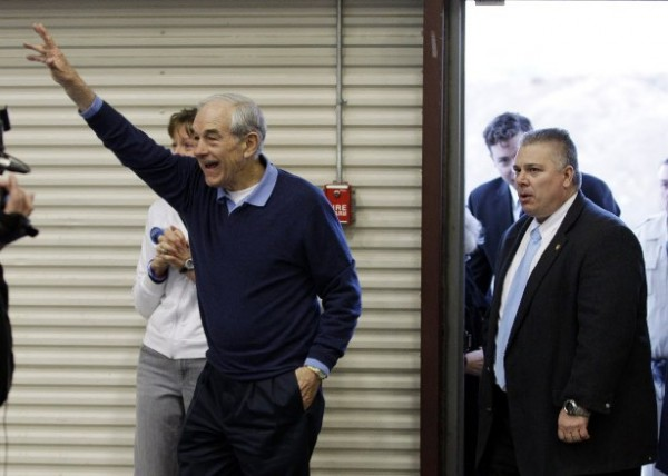 Republican presidential candidate Rep. Ron Paul, R-Texas, left, reacts to cheers from supporters as he arrives to speak at a rally Thursday, Feb. 2.