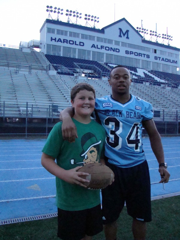 Roosevelt Boone (right) of the University of Maine poses with Will O'Neil of Orono, the son of faculty member Maryellen Mahoney-O'Neil, during a Black Bears football activity at Orono in 2010.
