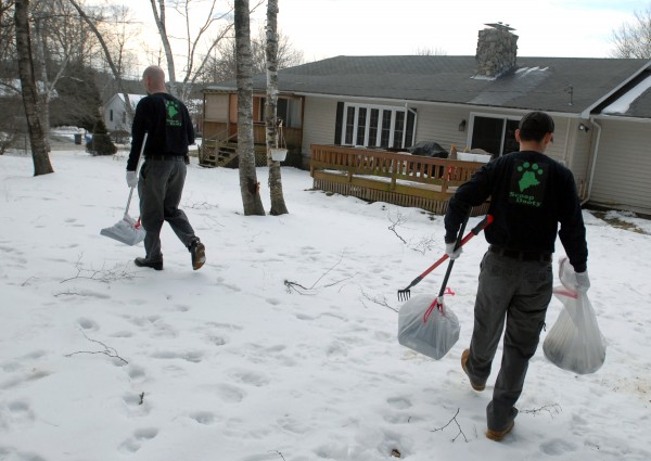 Jason Lubitz (right) and Justin Gibbons carry pet waste out of a client's yard in Bangor on Wednesday. Lubitz and Gibbons recently started their business called Scoop Dooty, a pet waste removal business.  The Bangor-based business opened last fall and is making Bangor cleaner by ridding yards of of pet waste.