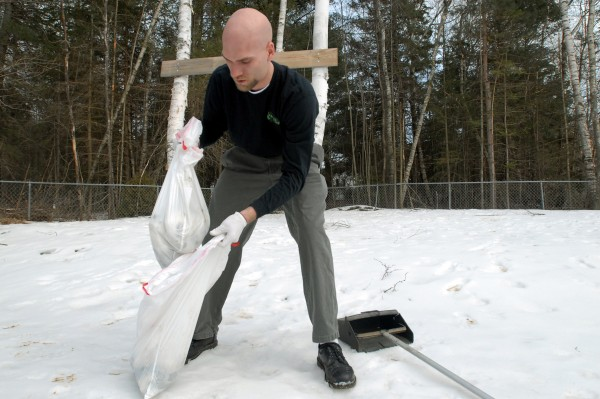 Justin Gibbons bags up pet waste to be removed from a client's yard on Wednesday.