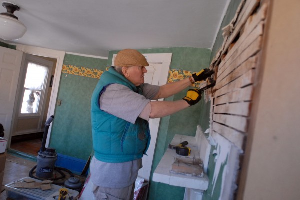 Tom Bartlett works in one of the bedrooms of his 1835 home that he and his wife Linda Stearns are renovating on Feb. 22, 2012. He is tearing off the horsehair plaster and lath wall to check the wiring and the chimney inside. Tom will then use drywall to complete the room.