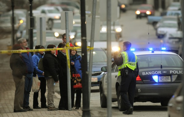 Spectators gather near the Bangor Public Library as police shut down the area while they investigate a suspicious package at the Margaret Chase Smith Federal Building in Bangor on Friday, Feb. 24, 2012.