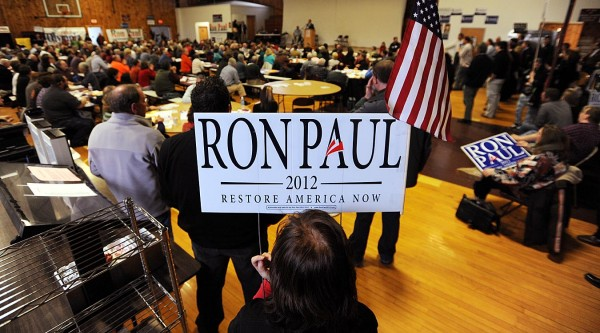 Standing in the back of the Washington Academy gym holding an American flag and a Ron Paul lawn sign, Elaine Ribeiro of Portland says she drove six hours to the Washington County Republican Super Caucus in East Machias to support presidential candidate Ron Paul.