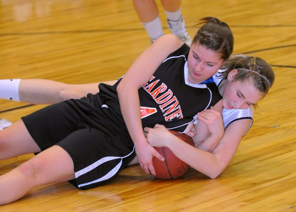 Gardiner Area High School's Kylee Granholm (left) and Presque Isle High School's  Hannah Graham wrestle for the ball during the first half of the Class B semifinal game at the Bangor Auditorium on Wednesday evening.