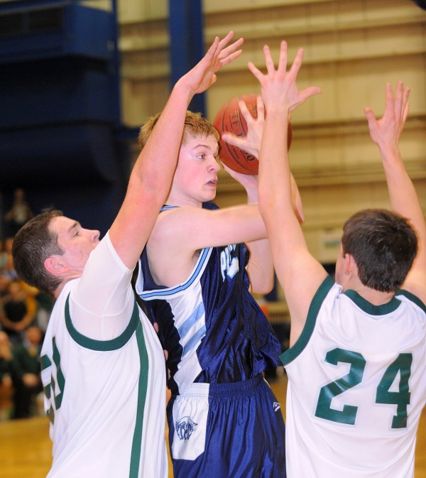 Presque Isle High School's Tyler Brooks (center) looks up for an open teammate as he is pressured by MDI High School's Adam Gray (left) and Caleb MacDonald during the second half of the Class B semifinal game at the Bangor Auditorium on Wednesday, Feb. 22, 2012.