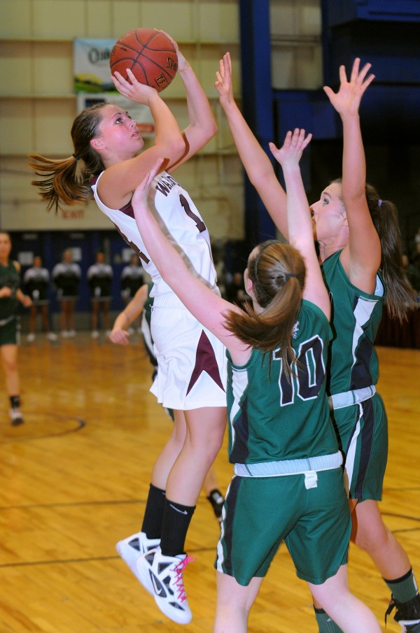 Nokomis Regional High School's Marissa Shaw (left) goes up for a shot over Old Town High School's Ashley Abbott (right) and Ashley England during the first half of the Class B semifinal game at the Bangor Auditorium on Wednesday evening.