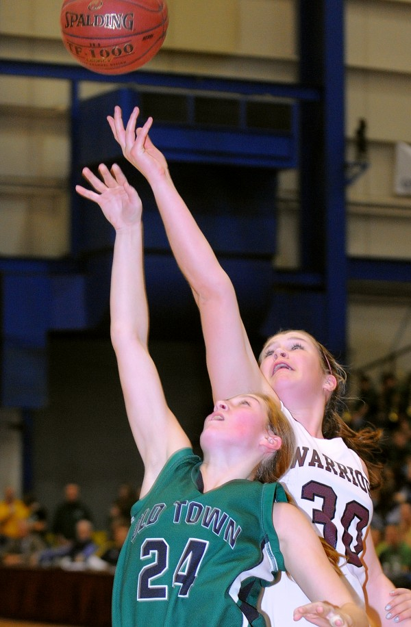 Old Town High School's Kelsey Hessletine (left) and Nokomis Regional High School's Anna Mackenzie go up for a rebound during the first half of the Class B semifinal game at the Bangor Auditorium on Wednesday evening.