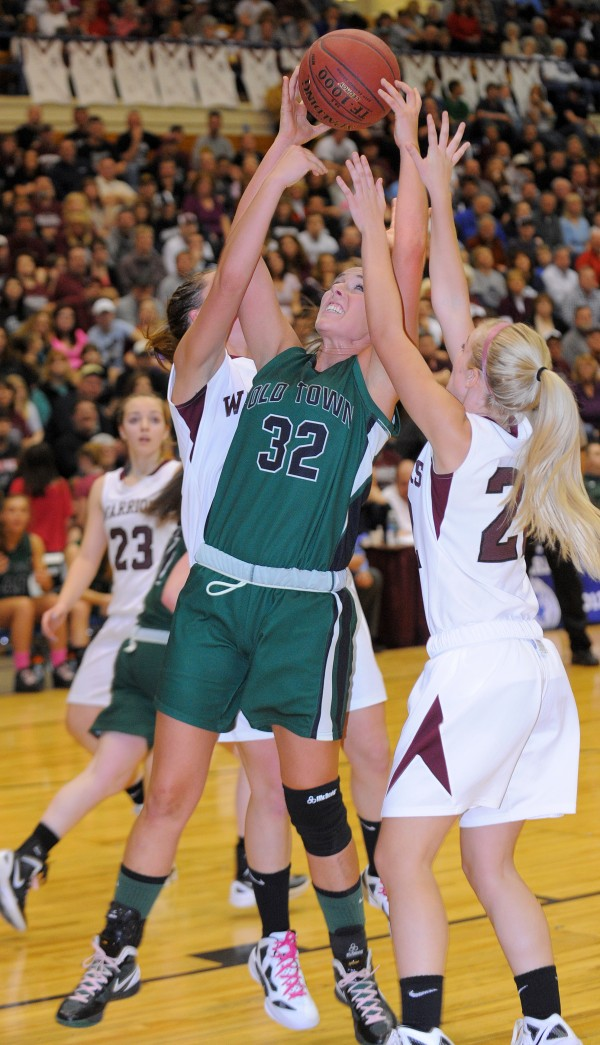 Old Town High School's Ashley Abbott (center) takes a rebound over Nokomis Regional High School's Lyndsay Whitney (right) and Marissa Shaw during the second half of the Class B semifinal game at the Bangor Auditorium on Wednesday evening.