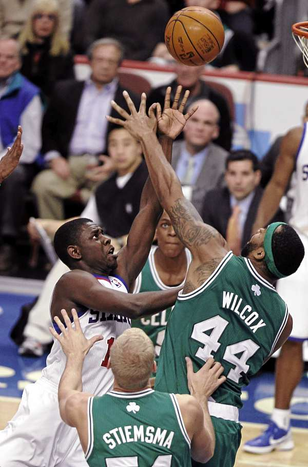 Philadelphia 76ers point guard Jrue Holiday (11) shoots as Boston Celtics forward Chris Wilcox (44) defends with the help of center Greg Stiemsma (54) in the second half of an NBA basketball game Wednesday night in Philadelphia. The 76ers won 103-71.