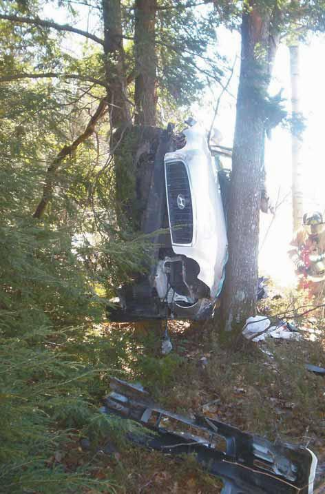 A Hyundai sedan driven by Richard Sandberg, who apparently suffered a seizure and veered off Interstate 295 northbound in Topsham on Saturday, March 10, 2012, lodged between trees after careening down an embankment and crashing. Rescue workers cut the roof off the vehicle to extricate Sandberg, who was taken to Maine Medical Center in Portland for treatment.