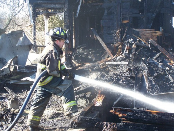 Forrest Mulheron of the Eddington Fire Department works a hose at 45 Rowell Road, the site of a Saturday morning farmhouse fire.