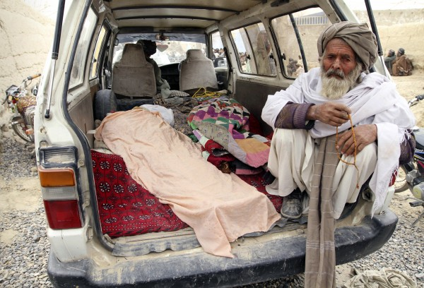 An elderly Afghan man sits next to the covered body of a person who was allegedly killed by a U.S. service member, in a minibus in Panjwai, Kandahar province south of Kabul, Afghanistan, Sunday, March 11, 2012. A U.S. service member walked out of a base in southern Afghanistan before dawn Sunday and started shooting Afghan civilians, according to villagers and Afghan and NATO officials. Villagers showed an Associated Press photographer 15 bodies, including women and children, and alleged they were killed by the American.