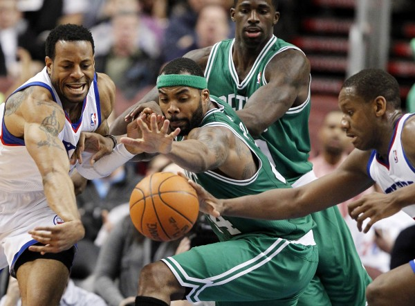 Philadelphia 76ers forward Andre Iguodala (left) and center Spencer Hawes (right) battle for a loose ball with Boston Celtics forward Chris Wilcox (center foreground) with Brandon Bass behind, during the first half of an NBA basketball game Wednesday, March 7, 2012 in Philadelphia.