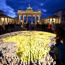 Volunteers of the World Wide Fund For Nature (WWF) place candles among about 5,000 candles to picture the globe prior to 'Earth Hour' in front of the Brandenburg Gate in Berlin on Saturday, March 31, 2012. Earth Hour takes place worldwide at 8.30 p.m. local time and is a global call to turn off lights for 60 minutes in a bid to highlight the global climate change.
