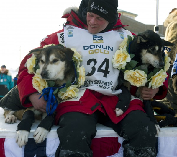 Dallas Seavey holds his leaders, Diesel, left, and Guiness after he arrived at the finish line to claim victory in the Iditarod Trail Sled Dog Race in Nome, Alaska, on Tuesday, March 13, 2012.  Seavey is the youngest musher to win the nearly 1,000-mile race across Alaska.