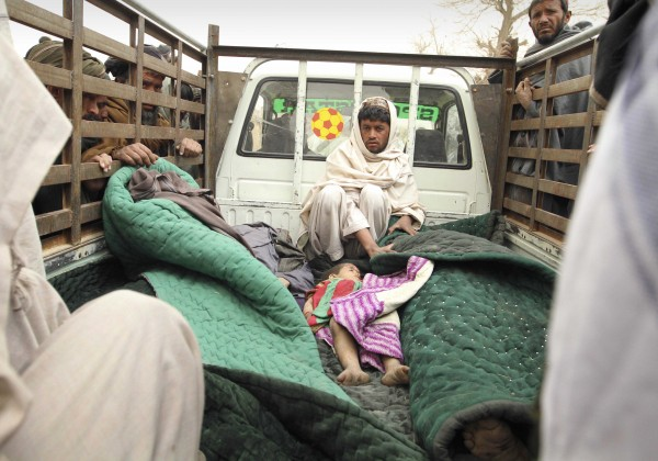 A man sits in the back of a truck with the bodies of  several men and a child allegedly killed by a U.S. service member in Panjwai, Kandahar province south of Kabul, Afghanistan, Sunday, March 11, 2012.