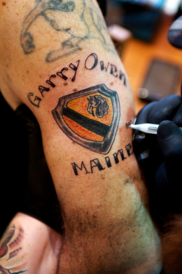 Curby Biagiotti of the Garry Owen Motorcycle Club gets the group's insignia tattooed on his arm in Chelsea Saturday afternoon, March 3, 2012, by an artist who asked not to be identified.