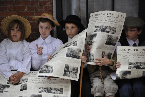 Fairmount School fourth-graders (from left) Alana Broughton, 10, Rya Morrill, 10, Brendan Martin, 10, Alexander Ogden (behind newspaper), 10, and David Rubin, 10, listen to other classmates as they take turns reading the headlines from a 1911 edition of the Bangor Daily Commercial during the class's history presentation at the Bangor Museum and History Center in June 2010.