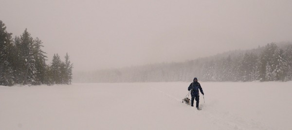 Chris Audet skis in a short but intense snow shower on the ice of Pogy Pond in Baxter State Park.