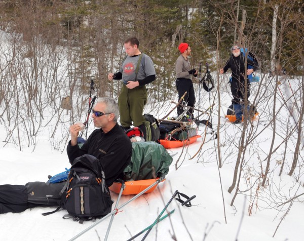 Nathan Scott (from left), Mike Mack, Jon Thurston and Glen Widmer eat lunch along the trail between South Branch Pond and Russell Pond camping areas in Baxter State Park on Friday, Feb. 24, 2012.