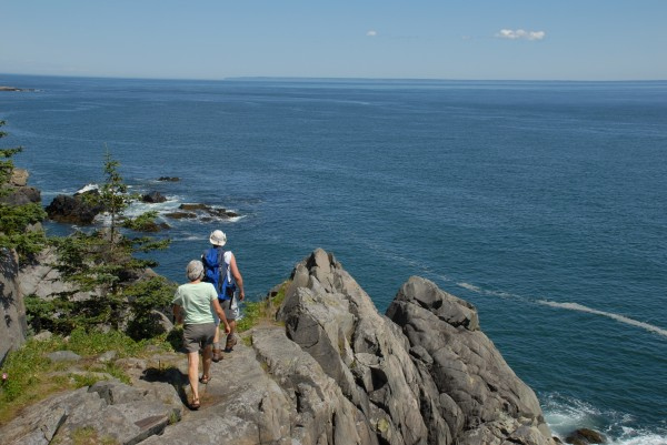 Two hikers step onto the rocky cliffs at the Bold Coast in Cutler. Among the four new degree programs recently announced by Husson University is a bachelor of science in hospitality and tourism management. This degree will provide students with high-level skills in guest service, tourism, and travel, all desirable skills in Maine's burgeoning tourism industry.