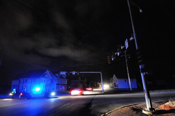 At the intersection of Wilson and Main Streets, a Brewer police officer directs traffic under one of many nonfunctioning traffic lights during Monday night's power outage in Brewer.