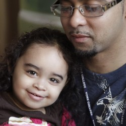 Cristina Astacio, 2, recently diagnosed with a mild form of autism, reacts as reads with her dad Christopher Astacio on Wednesday, March 28, 2012 in New York.  Autism cases are on the rise again, largely due to wider screening and better diagnosis, federal health officials said Thursday, March 2012.