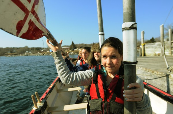 Rockland Middle School seventh-grader Emily Hutchinson hands oars forward to be put away on Tuesday during crew practice.