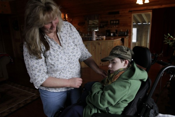 Ethan Kelly, 21, who has cerebral palsy, gets help from his mother, Lisa Kelly, in Appleton, Maine, on Wednesday, March 28, 2012. Ethan's parents, Alden and Lisa Kelly provide full-time care for their son.
