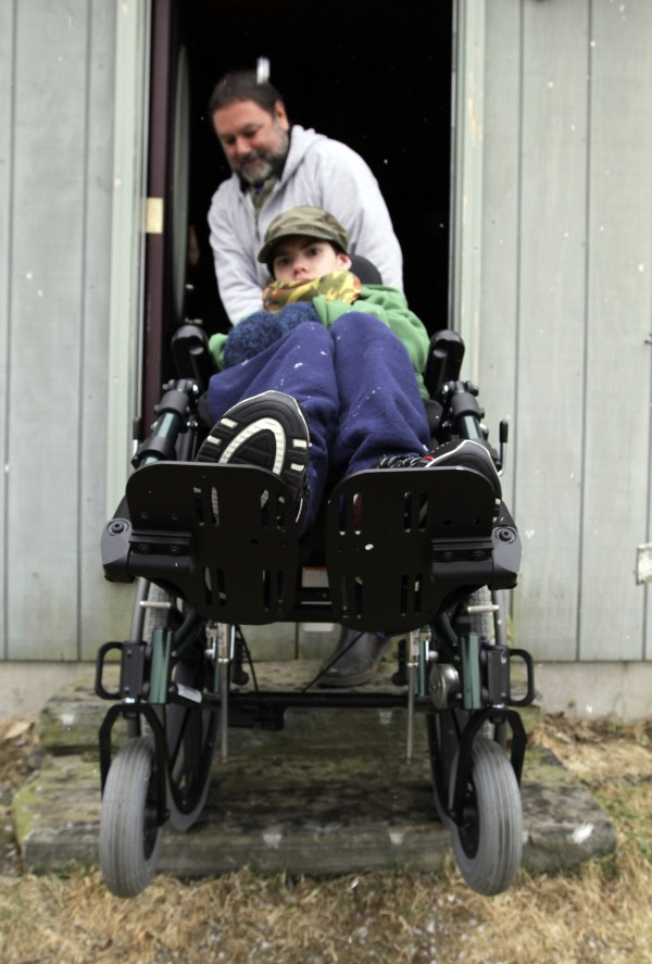Ethan Kelly, age 21, who has cerebral palsy, is wheeled out of his home by his father, Alden Kelly, in Appleton, Maine, on Wednesday, March 28, 2012.