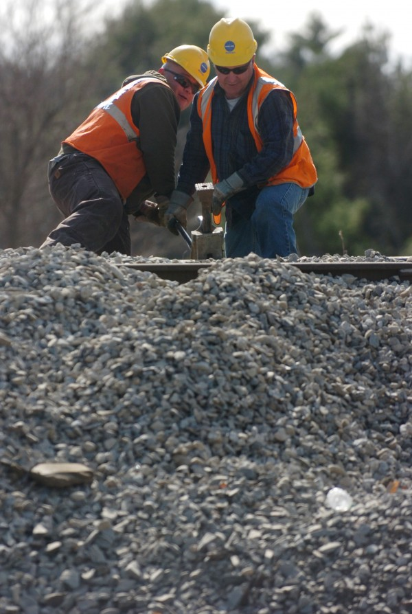 Pan Am rail workers pry up rail to repair part of the washed out rail line with new gravel fill. Friday evening's dam breach in Orrington led to heavy washout under the Swetts Pond Road and under the rail line along River Road.