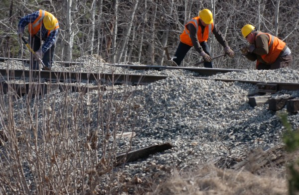 Pan Am rail workers pry up rail to repair part of the washed out rain line with new gravel fill.