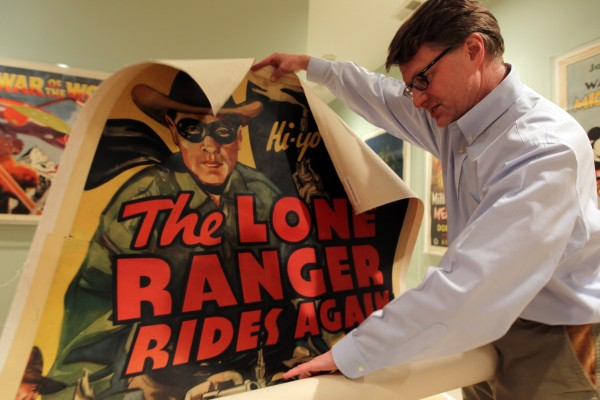 Movie poster collector Dwight Cleveland unrolls a poster for &quotThe Lone Ranger Rides Again&quot at his home in Chicago, Ill., March 6, 2012.