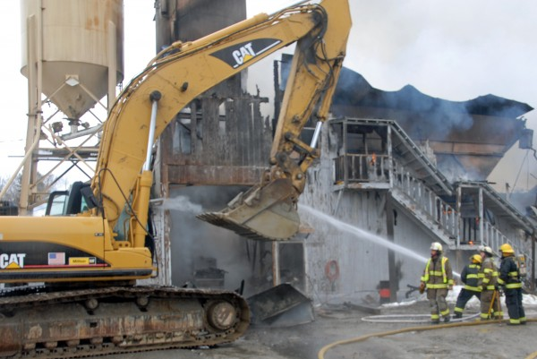 East Millinocket and Medway firefighters work with a backhoe to save equipment at a fire that destroyed a concrete factory off Route 11 in East Millinocket on Friday, March 16, 2012.