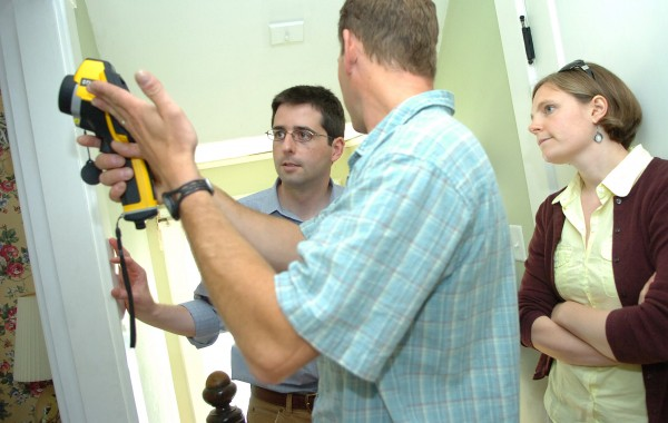 Matthew Damon with Penobscot Home Performance (center) talks with Bangor homeowners Keith and Beth Bisson while performing a home energy audit using an infrared camera in June 2010.