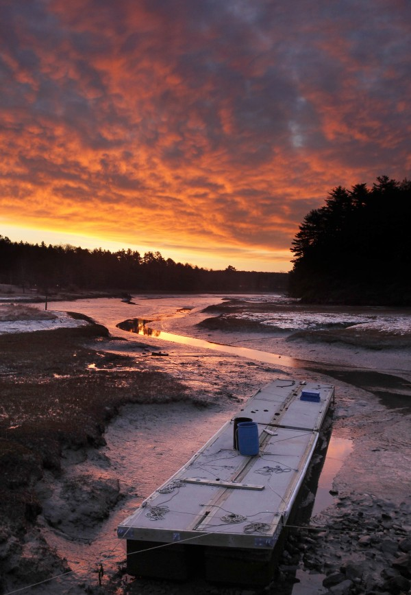The morning sky glows red over the north end of the Harraseeket River where a floating dock sits on the mud at low tide on Monday, March 12, 2012.