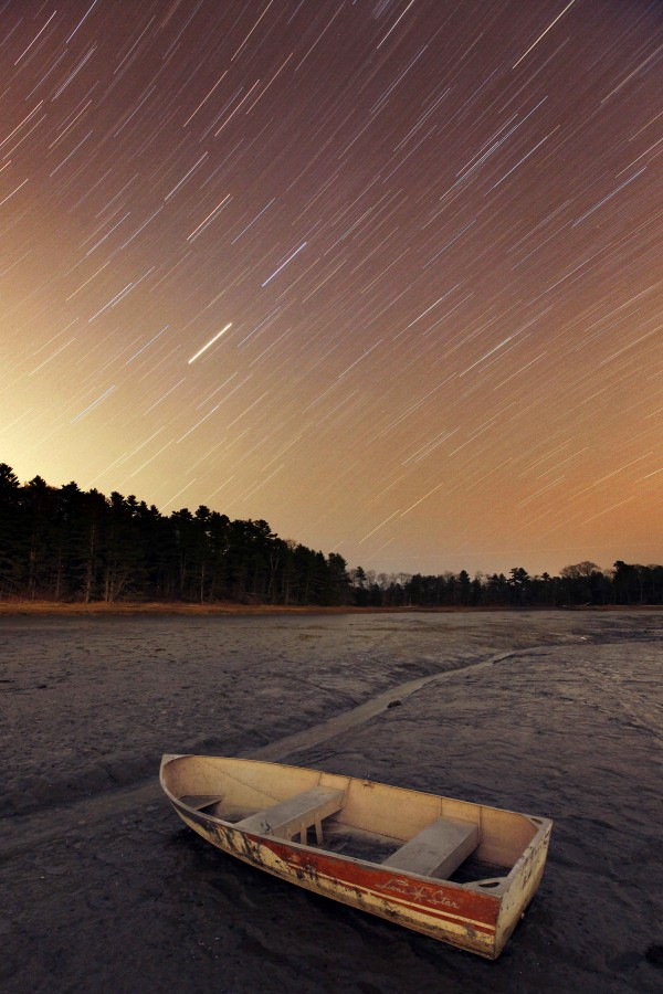 Stars rotate through the evening sky over Harraseeket River where a skiff sits on the mud at low tide in Freeport.