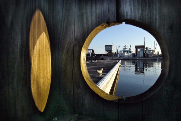 An opening in a small wooden shelter frames a view of fishing boats docked at Harraseeket River in Freeport. Less than a dozen boats remained in the water for the winter.