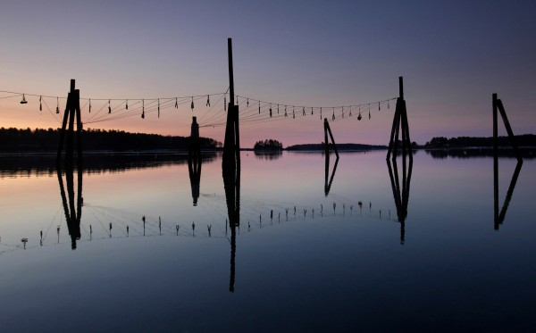 Pilings reflect in still water at dawn at the Harraseeket Yacht Club in Freeport. The floating docks were removed for winter.